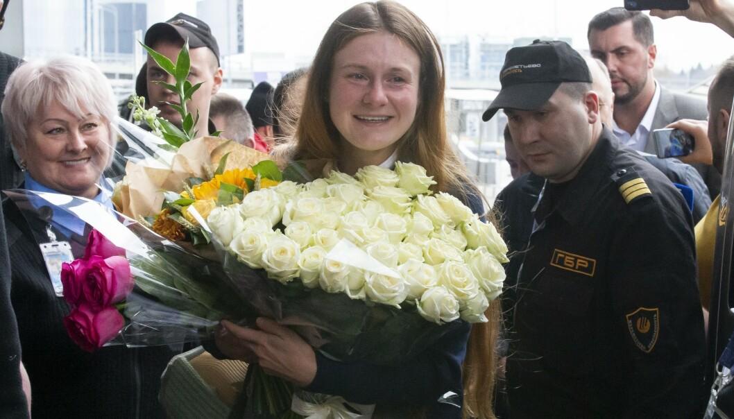 Russiske Maria Butina fikk overrakt blomster da hun ankom Moskva lørdag. I Russland er hun blitt et symbol på det mange russere oppfatter som «russerfobi» i USA. Foto: Aleksandr Zemljanitsjenko / AP / NTB scanpix