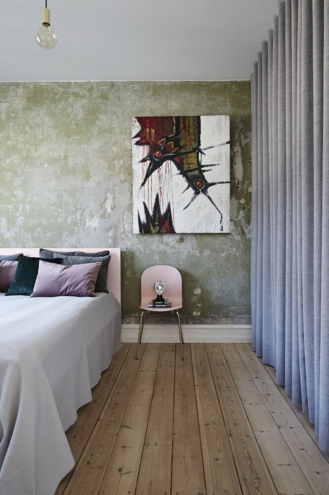 Da Christina og Jan fjernet det gamle tapetet på soverommet, kom den grønne, rå veggen til syne. Bak gardinene henger klærne deres. Sengeteppet er fra H&M Home, gardiner og puter fra &Drape, stolen fra Ellos.dk, bordlampen fra Beau Marché, mens kunstverket er laget av Lasse Bekker Weinreich. Tips! En kontrastvegg – enten den er malt i en annen farge eller den er en rå murvegg som her – gir ekstra dynamikk til et rom. FOTO: Stylesystemet