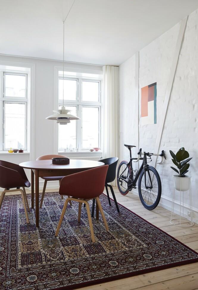 I spisestuen står et fint teakbord som er funnet på loppemarked. Paret har satt moderne stoler fra Hay rundt for å skape en kontrast. Teppet er fra Ikea, og den klassiske PH-lampen har de arvet. Tips! La en mursteinsvegg stå hvitkalket eller hvitmalt, og fest noen brede lister loddrett og på skrå på veggen, så ligner det på bindingsverk. FOTO: Stylesystemet