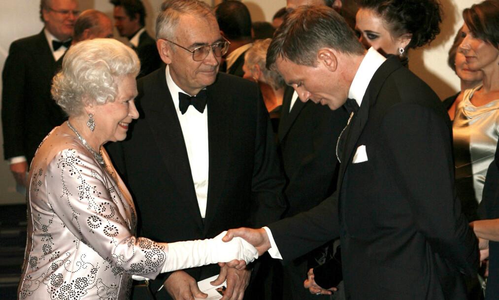 OPPSIKTSVEKKENDE DETALJER: I en ny bok skrevet av dronning Elizabeths personlige assistent, venn og draktsyer, Angela Kelly, kommer det frem flere hemmeligheter om den britiske monarken. Her er hun avbildet sammen med Hollywood-stjernen Daniel Craig i 2006. Foto: NTB Scanpix