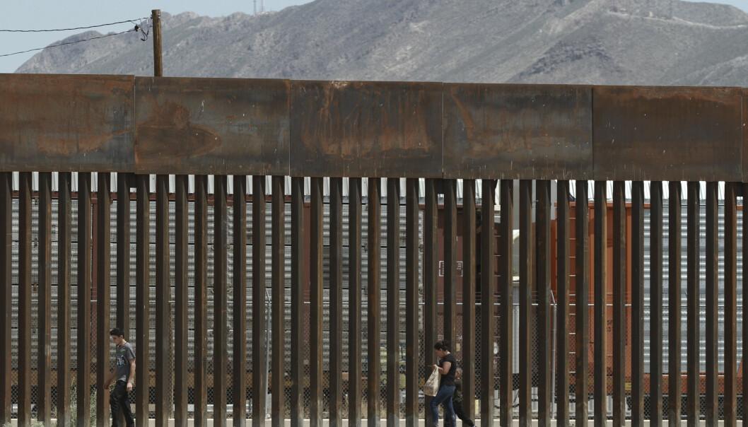 Migranter foran en av murene som allerede er bygget langs grensa mellom USA og Mexico. Foto: Christian Chávez / AP / NTB scanpix.