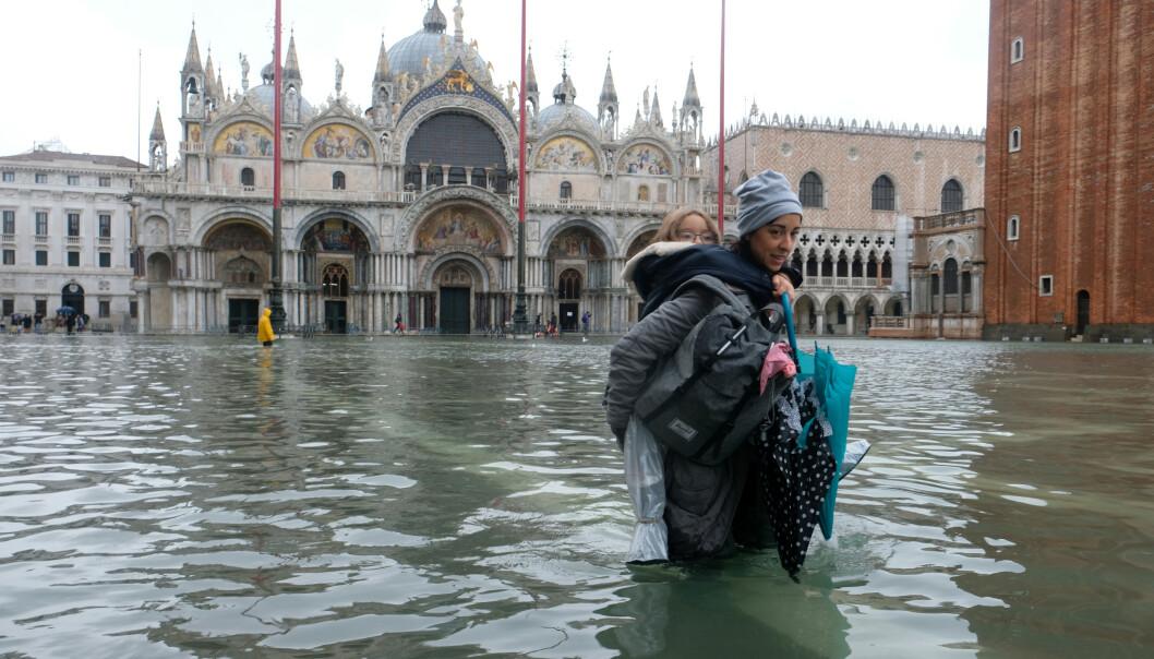 <strong>UNDER VANN:</strong> En kvinne bærer barnet på ryggen, mens vannet når henne til over knærne på Markusplassen. Foto: Reuters/Manuel Silvestri