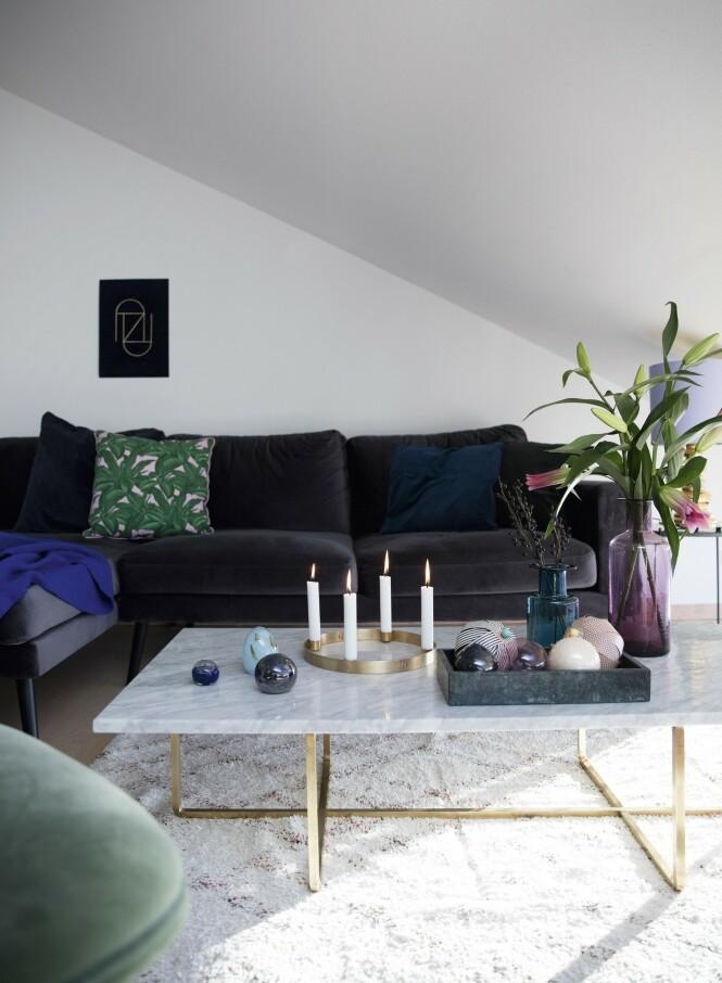 Den grå sofaen fra BoConcept og det hvite bordet fra Ox Denmarq gir en rolig base som Nynne har gitt farge med puter, tepper, lamper og vaser. Vegglampen som er et helt kunstverk i seg selv, er fra Please Wait to be Seated. Den blå plakaten i velur er Nynnes eget design, og den grønne stolen er fra Gubi. FOTO: Kira Brandt