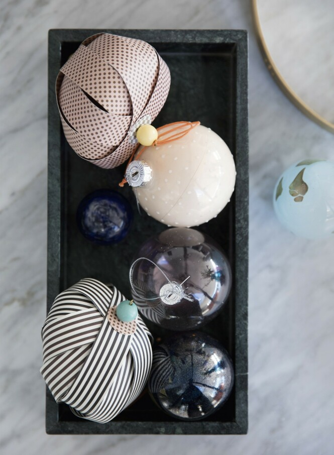 Nynne er glad i å blande skjør glasspynt med   papirkuler som med striper og trykk understreker den grafiske stilen. Tips! Hvis du har et møbel med metalldetaljer, som for eksempel et sofabord med messingbein, kan du la det samme metallet gå igjen på detaljer som bestikk, lysestaker og gaveinnpakning. FOTO: Kira Brandt