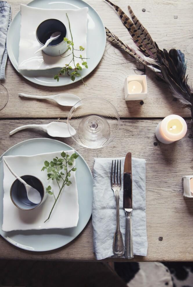 Hvitt servise, telysholdere og bestikk fra Bolina. Lyseblå tallerkener fra Serax og tøyservietter fra fra H&M Home. FOTO: Yvonne Wilhelmsen