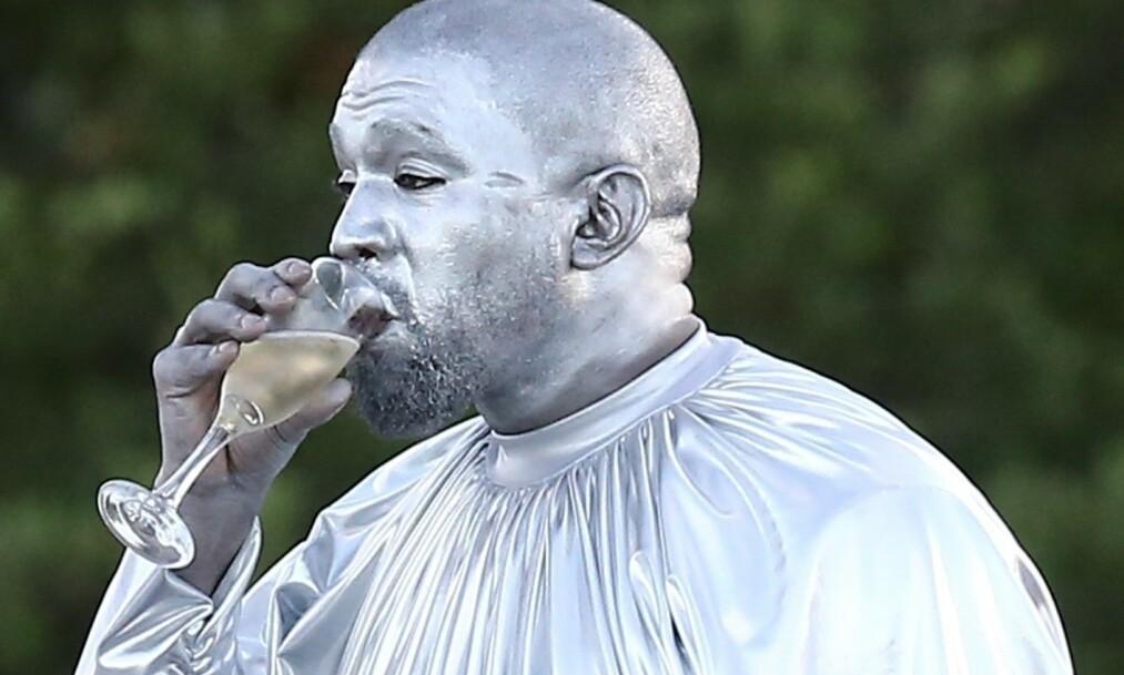 SKÅL: Kanye West malte seg like så godt sølv, og nøt et bedre glass champagne foran fotografene. Det er derimot ikke helt uten grunn at han valgte den noe spesielle looken. Foto: NTB scanpix