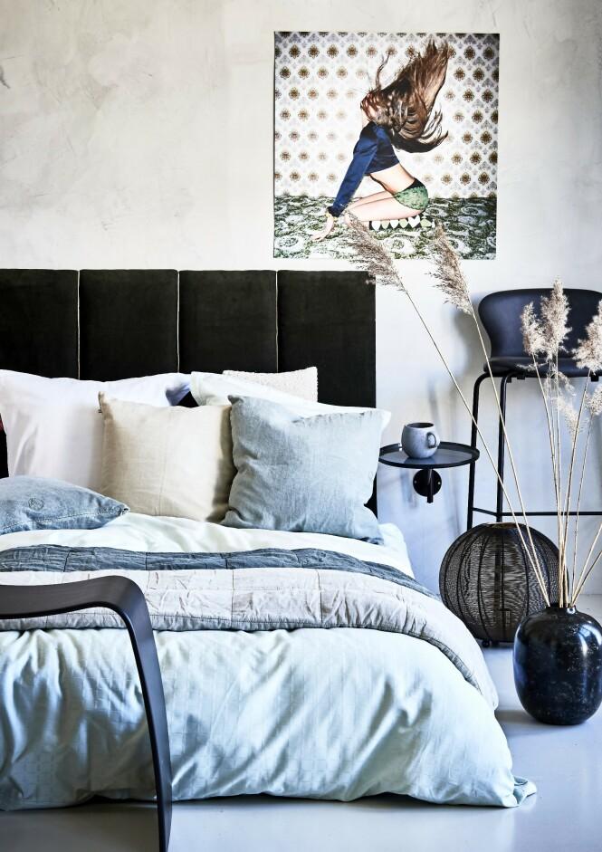 Sengetøy (Södahl). Hvite linputer (House Doctor). Beige pute, grågrønne puter, grågrønt sengeteppe og sandfarget sengeteppe, alt fra Sika Design). Lysegrønt sengetøy (Södahl). Svart skammel (Askman). Gulvvase, gulvlampe, vegghengt hylle og kopp (alt fra Bloomingville). Barstol (Bruunmunch). Plakat (Paper Collective). Fløyel (Stoff & Stil). Papirgarn (Balderus Stoleflet). Lekter og MDF-plater er kjøpt på et byggevarehus. Veggen har fått en betonglook med maling i fargen «Washed Linen» fra Jotun. FOTO: Martin Panduro