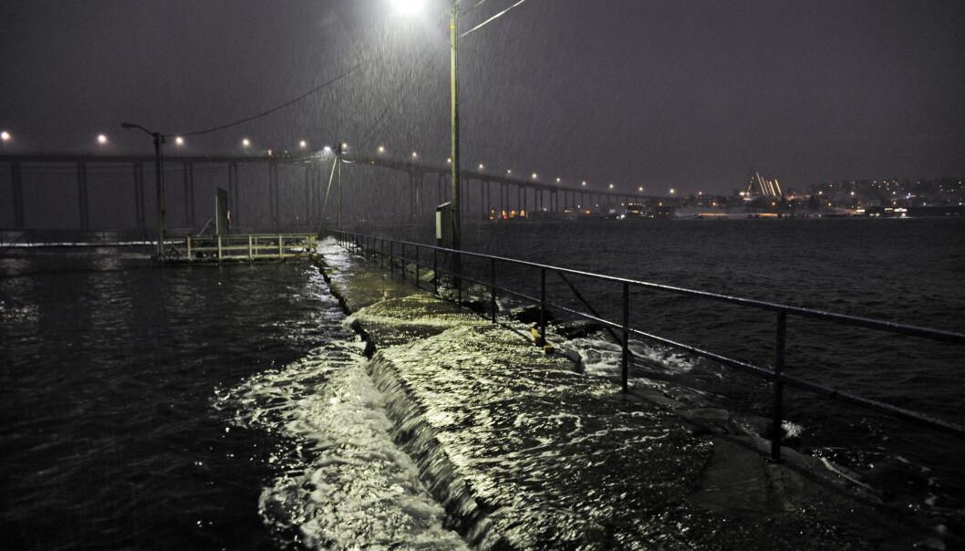 Uværet feier inn over Norge lørdag. Storm i kastene og nedbør. Her fra Tromsø havn ved en tidligere anledning, da bølgene slo over moloen. Ishavskatedralen skimtes i bakgrunnen. Arkivfoto: Rune Stoltz Bertinussen / NTB scanpix.