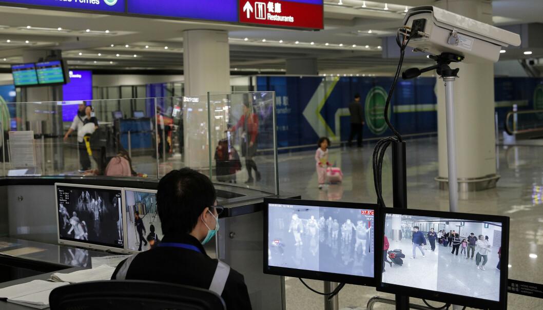 En flyplassmedarbeider holder oppsyn med passasjerer som ankommer flyplassen i Hongkong. Myndighetene har innført tiltak for å forhindre at lungesykdommen som har spredt seg i Fastlands-Kina skal spre seg. To personer er bekreftet døde av viruset. Foto: Andy Wong / AP / NTB scanpix.