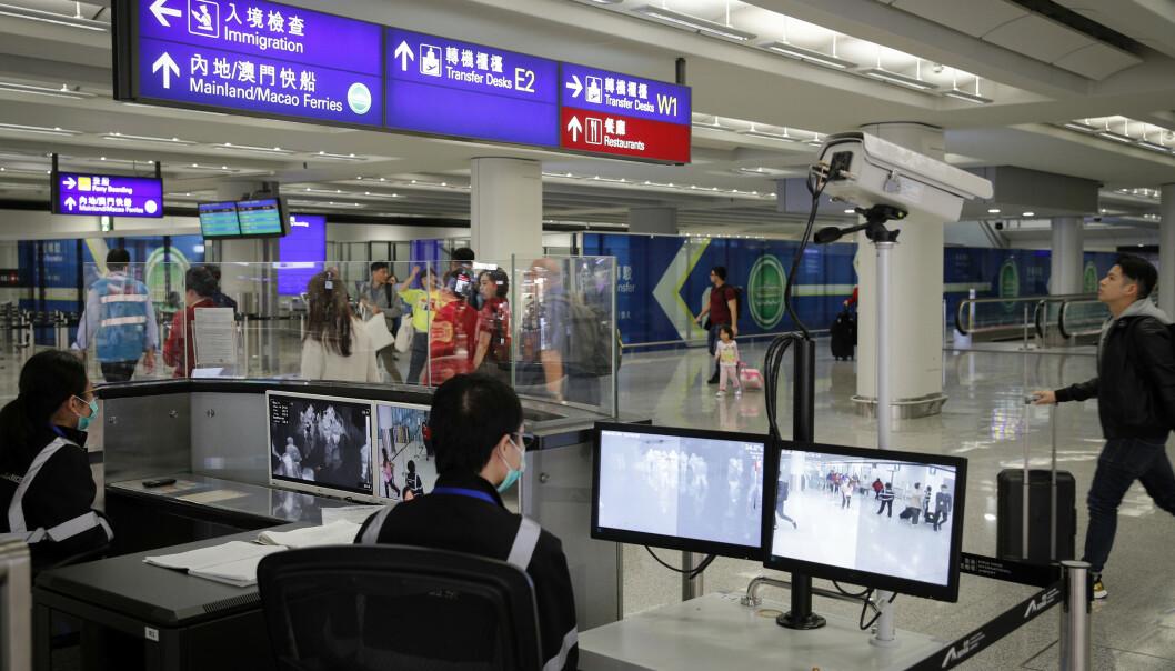 En tjenestemann overvåker passasjerer ved ankomsten til den internasjonale flyplassen i Hongkong, på leting etter tegn til sykdom. Bildet er tatt 4. januar. Et utbrudd av et luftveisvirus i Kina har ført til frykt for spredning. Foto: Andy Wong / AP / NTB scanpix.