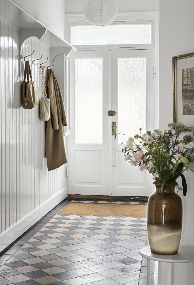 Annas smak når det kommer til farger, vises også i gangen, der vesker og ytterklær går ton i ton med de øvrige fargetonene i hjemmet. Veggpanelene og gulvet er originale fra da huset ble bygd. FOTO: Peter Kragballe