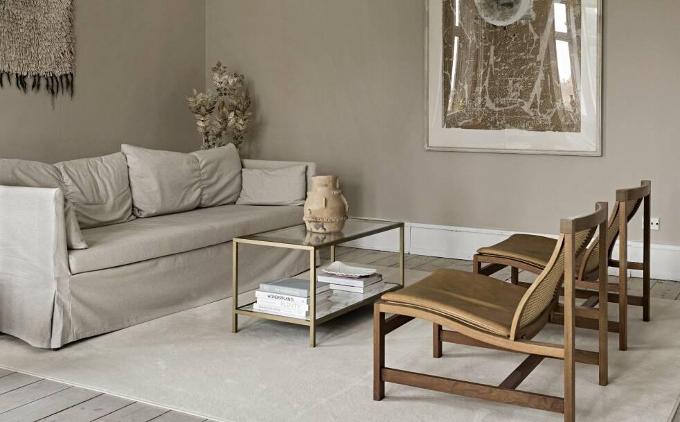 Sofaen, som heter Sandbacken og er fra Ikea, går nesten i ett med veggen, mens bordet og lampen i messing skaper en fin kontrast. FOTO: Peter Kragballe