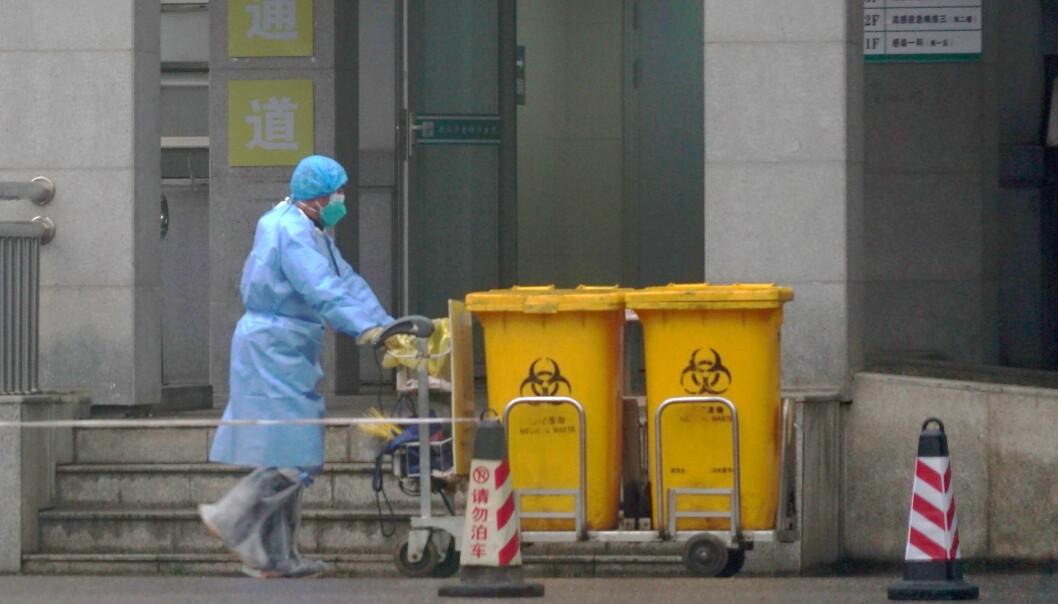 En ansatt flytter på søppelbøtter med biologisk avfall ved et medisinsk senter i Wuhan, der virusutbruddet trolig startet. Foto: AP / NTB scanpix