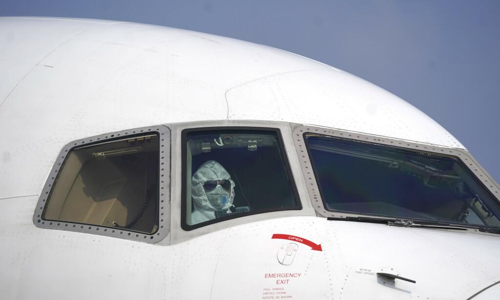 STOPPER: En pilot i et fly på flyplassen i Wuhan i Kina, episenteret for Wuhan-viruset, tirsdag. Flere flyselskap stopper nå alle sine direktefly til Kina som følge av utbruddet av den dødelige varianten av coronaviruset som er påvist i landet. Foto: Cheng Min/Xinhua/ AP/ NTB scanpix