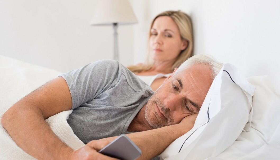 FINN EN FEIL: Tar du med deg telefonen i senga? Det kan skape trøbbel i parforholdet. Foto: Scanpix.