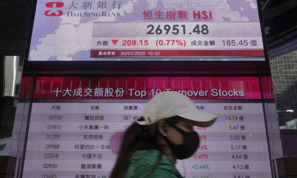 FALLER: Bekymring rundt utbruddet av den nye virussykdommen i Kina har ført til nedgang på flere asiatiske børser. Her går en kvinne forbi en elektronisk tavle som viser Hongkong-indeksen. Foto: AP / Vincent Yu / NTB scanpix