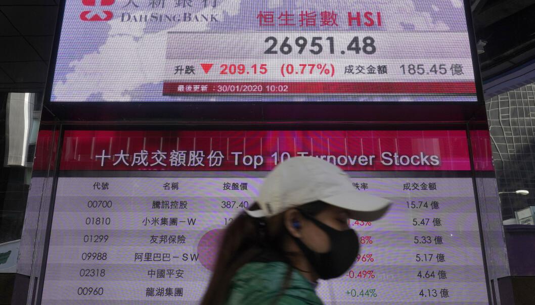 <strong>FALLER:</strong> Bekymring rundt utbruddet av den nye virussykdommen i Kina har ført til nedgang på flere asiatiske børser. Her går en kvinne forbi en elektronisk tavle som viser Hongkong-indeksen. Foto: AP / Vincent Yu / NTB scanpix