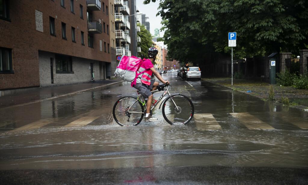 Et bud fra Foodora sykler gjennom vannmasser i Vahls gate i Oslo. Foto: Berit Roald / NTB scanpix