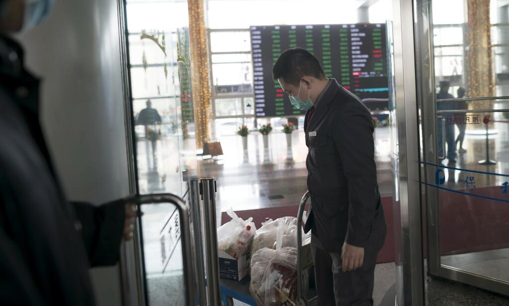 En ansatt med ansiktsmaske i foajeen på Shanghai-børsen mandag. Foto: AP / NTB scanpix