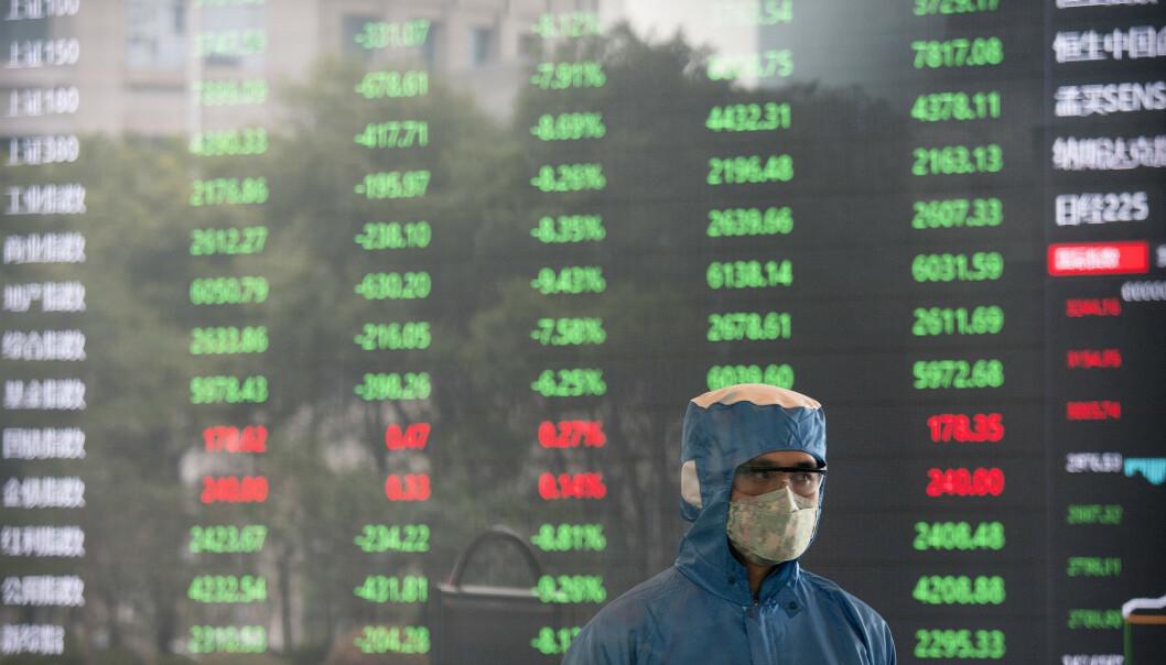 <strong>VIRUSFRYKT:</strong> En ansatt med ansiktsmaske og drakt på Shanghai-børsen tirsdag. Foto: AP / NTB scanpix