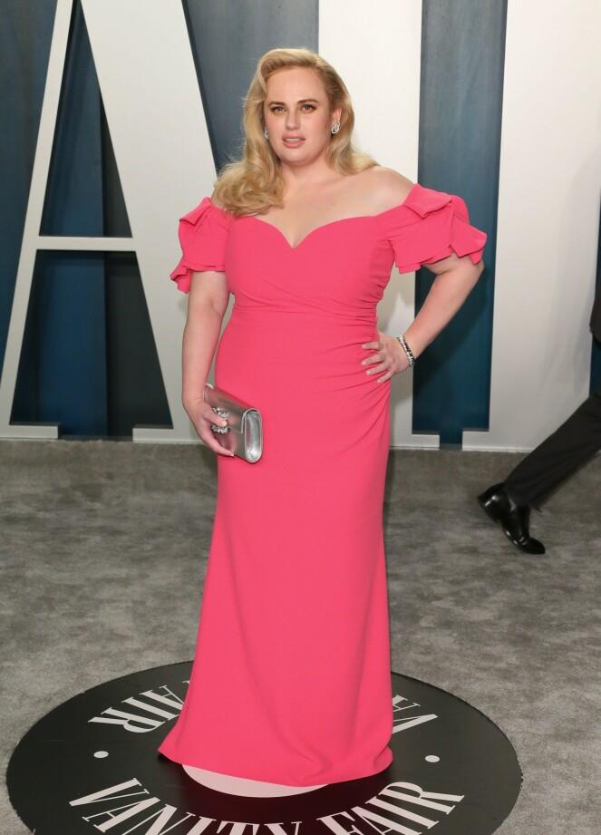 <strong>LYSTE OPP:</strong> Skuespiller Rebel Wilson gikk for en sterk rosafarget kjole med en sølvfarget veske til. Foto: NTB Scanpix