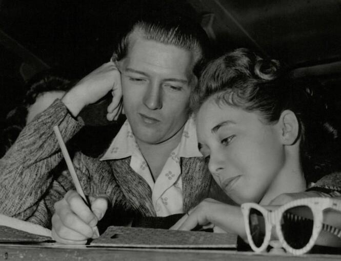 FORELSKET: Jerry Lee Lewis kaster et forelsket blikk mot kona Myra, som skriver i noe som kan se ut som kladdebøker. Bildet er tatt i 1958. FOTO: NTB scanpix
