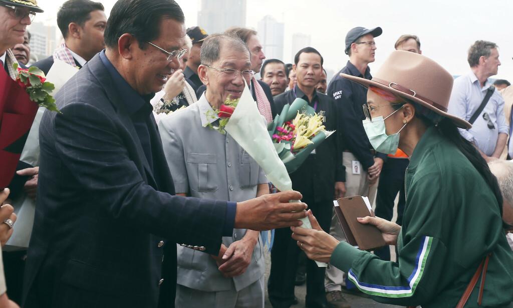 Kambodsjas statsminister Hun Sen delte ut blomster til passasjerer som fikk forlate cruiseskipet Westerdam. Foto: Heng Sinith / AP / NTB scanpix
