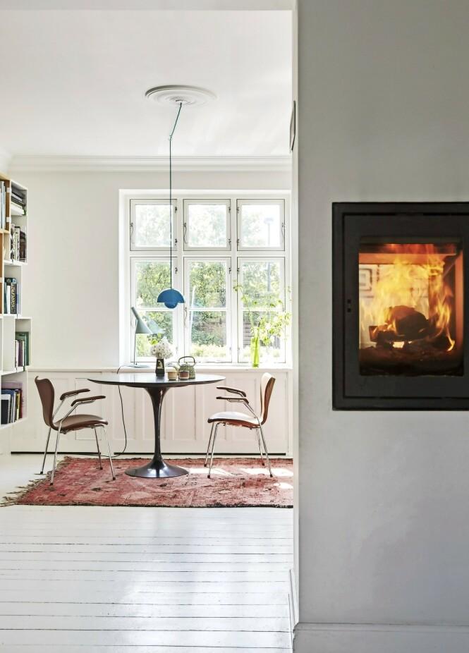 En kikk inn på kjøkkenallrommet. Bordet er designet av Eero Saarinen, stolene av Arne Jacobsen, og «Flowerpot»lampen over bordet av Verner Panton. Tips! En peis som står midt i rommet og som har glass i begge ender, lar lys og flammer spre seg til hele rommet. FOTO: Anitta Behrendt