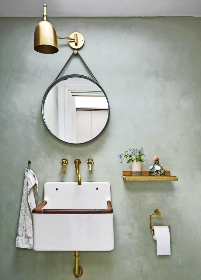 Veggen på badet har fått et støvete, grønt uttrykk. Den er malt med det som kalles stucco lustro, som betyr lysende puss. Dette er maling som inneholder knust marmor, noe som gir veggen et fascinerende fargespill. Vasken er fra en gammel skole. FOTO: Anitta Behrendt
