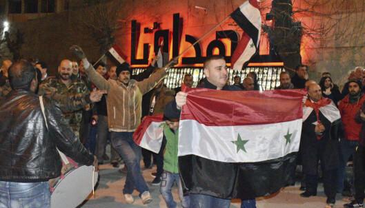 Syrere feirer regjeringshærens framrykking i provinsen Aleppo. Bildet er publisert av det statlige syriske nyhetsbyrået Sane. Foto: Sana via AP (NTB scanpix