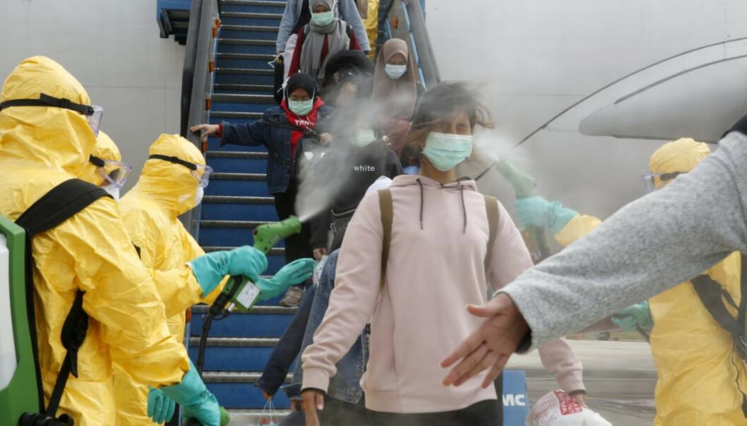 <strong>STORE RINGVIRKNINGER:</strong> Indonesiske flypassasjerer sprayes etter å ha ankommet fra Wuhan, hvor coronaviruset oppsto. Nå kan viruset påvirke det norske lønnsoppgjøret. Foto: Antara Foto/via Reuters / NTB Scanpix