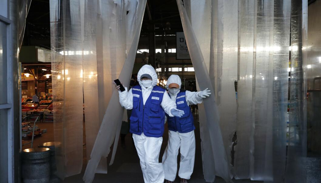 <strong>SYNKER:</strong> Frykten for konsekvensene av virusutbruddet førte til nok en dag med nedgang på børsene i Asia. Her er arbeidere på vei inn for å desinfisere et marked i Sør-Koreas hovedstad Seoul. Foto: Lee Jin-man/ AP/ NTB scanpix
