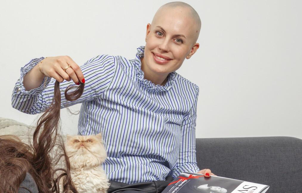 KREATIV: Katten synes det er spennende med de mange parykkene Julia har. Som spesialkontakt i Alopeciaforeningen Norge holder hun seg oppdatert ved å lese foreningens internblad «Hei Sveis». Foto: Svend Aage Madsen/ Se og Hør