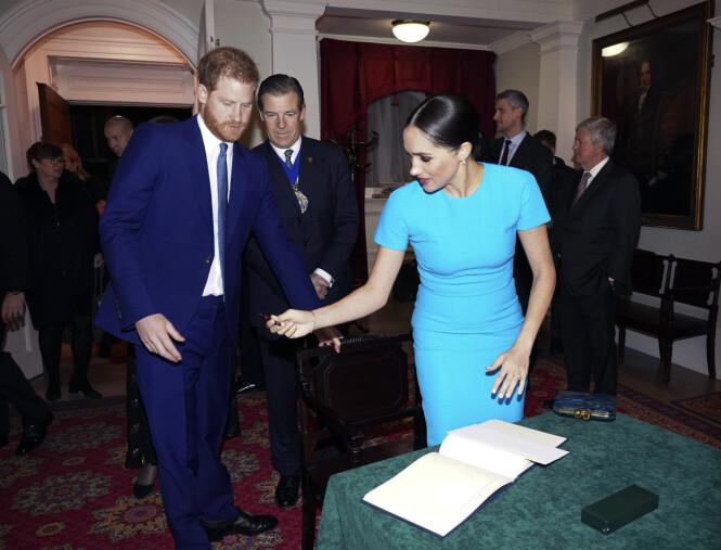 I FORTROPPEN: Meghan gir ektemannen pennen slik at han kan signere gjesteboken under Endeavour Fund Awards i London 5. mars 2020. FOTO: NTB scanpix