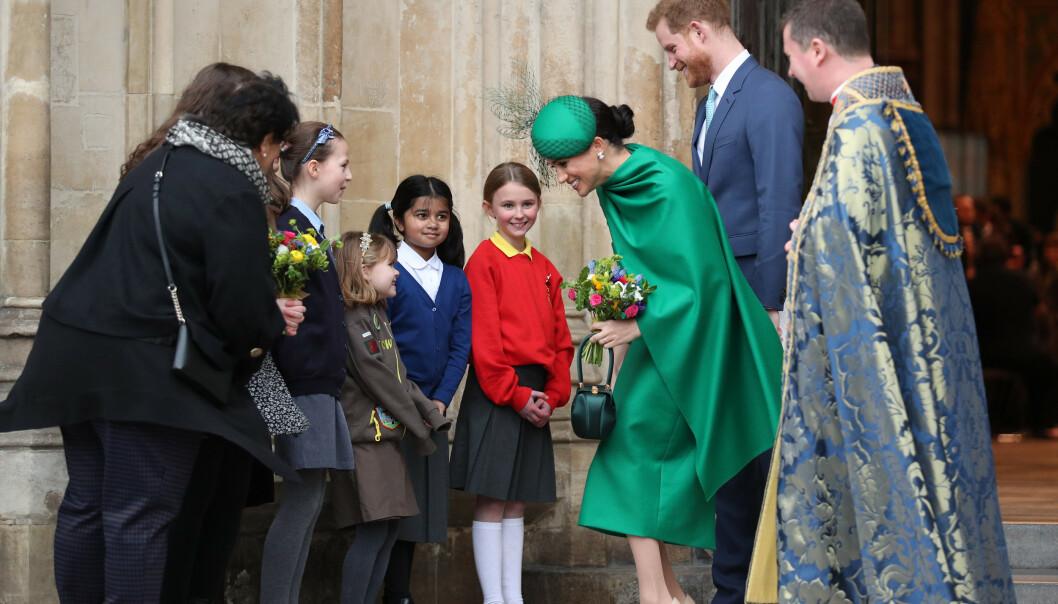 HILSER: Hertugparet tok imot en blomsterbukett fra skoleelever på vei ut fra markeringen inne i Westminister Abbey. Foto: NTB scanpix