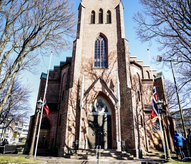 I 11-TIDEN: Flagg på halv stang foran Tønsberg domkirke i formiddagssol.