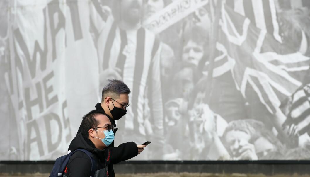 MASKER: Mennesker fotografert med masker utenfor St. James Park i England 14. Mars. Foto: NTB Scanpix
