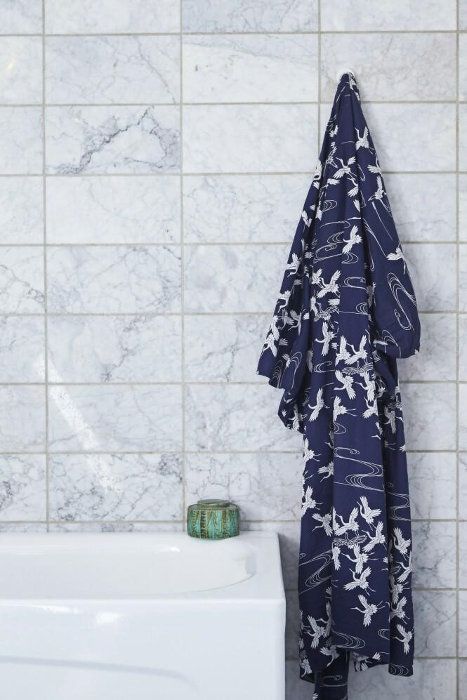 Badet er enkelt i uttrykket med de originale marmorflisene fra 1980-tallet. Kimonoen er fra den japanske butikken Boutique Taeko, og den grønne krukken tilhørte Snorres besteforeldre og fulgte med huset. FOTO: Ditte Capion