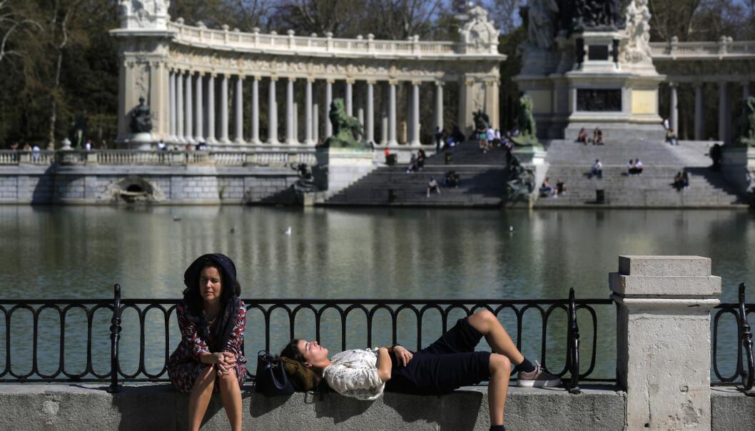 Folk nyter sola i Retiro-parken i Madrid lørdag. Statsminister Pedro Sanchez sier at regjeringen vil erklære en to uker lang krisetilstand. Det vil gi myndighetene omfattende fullmakter, som inkluderer mobilisering av hæren, i kampen mot koronaviruset. Foto: AP / NTB scanpix
