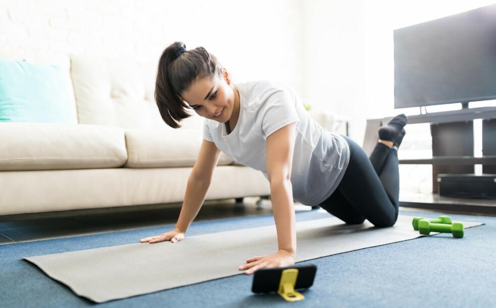 HJEMMETRENING: På nett kan du finne en rekke effektive treningsøkter du kan gjøre hjemme i stua. Alt du trenger å gjøre er å finne frem mobilen og sette i gang. FOTO: NTB Scanpix