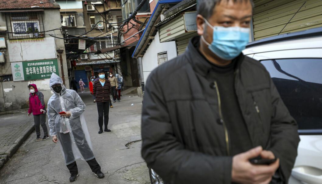 Folk i står i god avstand i kø for å kjøpe kjøtt på et marked i Whuan. Snart blir de strenge restriksjonene i byen lempet. Foto: AP / NTB scanpix