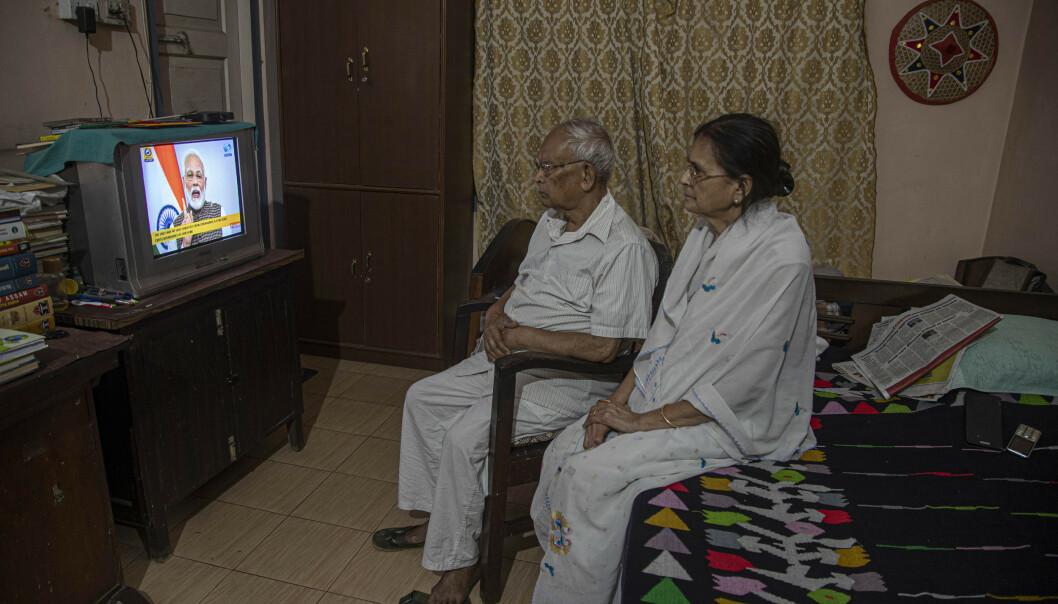 Et eldre indisk par ser på statsministeren Narendra Modis tale der han kunngjorde portforbud i hele landet tirsdag. Foto: Anupam Nath / AP / NTB scanpix