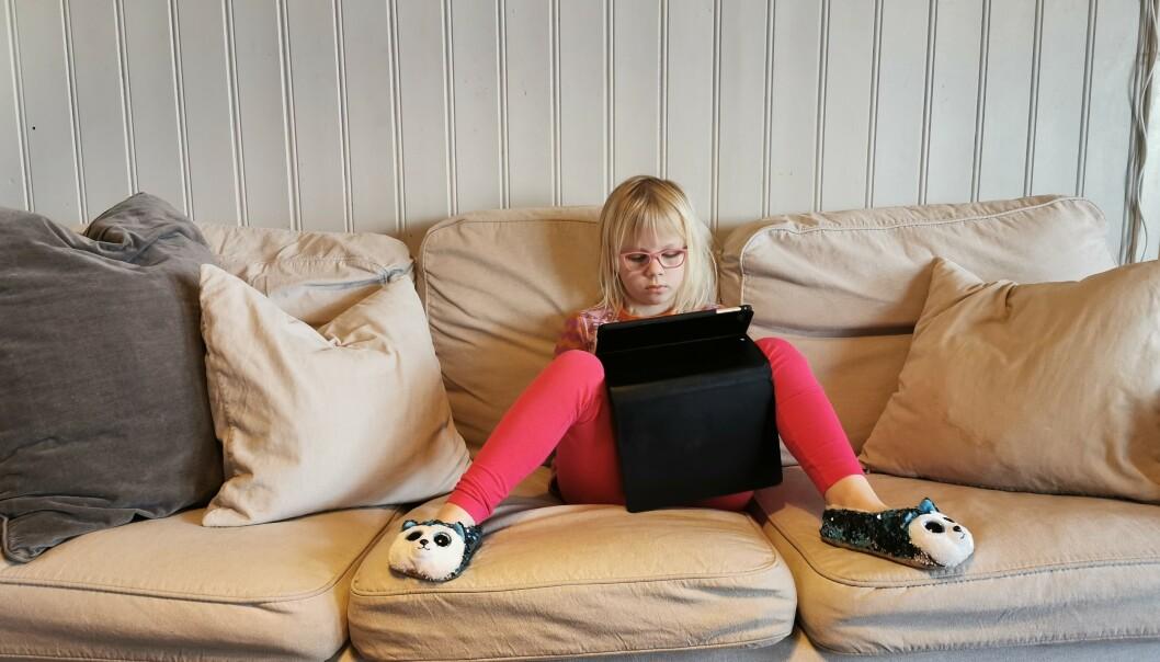 SOFASKOLE: Dorotea er ganske avslappet der hun har funnet sin plass i sofaen, med nettbrettet på fanget. FOTO: Privat