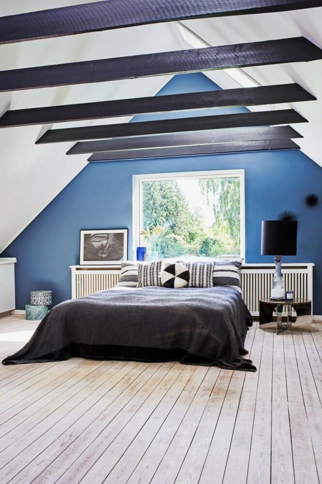 En ekstra lang radiatorskjuler fungerer både som utvidet vinduskarm og sengegavl på det store soverommet. Bord og lampe er fra Design by Us, veggpynt fra Mojoo og bokser fra Søstrene Grene. Tips! Ikke vær redd for å henge opp bilder, plakater og fotografier på veggene. Det gir karakter til hjemmet. FOTO: Høeg + Møller