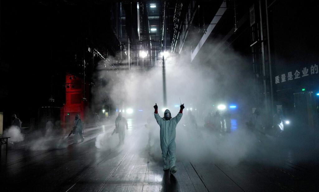 DESINFISERER: Frivillige fra Blue Sky Rescue-teamt jobbet 2. april med å desifisere Qintai Grand- teateret i Wuhan. Foto: REUTERS / Aly Song / NTB scanpix