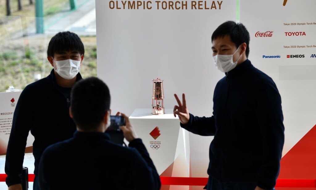 People take pictures of the Olympic Flame which was passed from Tokyo 2020 to Fukushima Prefecture at the J-Village National Training Centre in Naraha on April 2, 2020. (Photo by Kazuhiro NOGI / AFP)