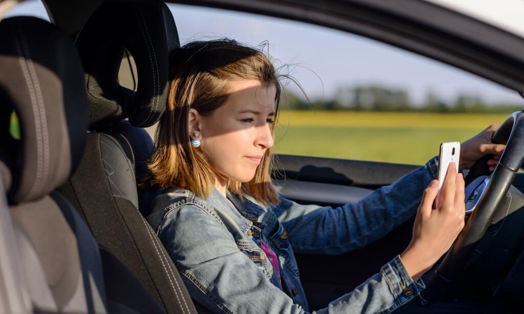 IKKE «UNDER KJØRING»: Når bilen sto stille i kø, kan ikke kvinnen ilegges bot for «bruk av håndholdt mobiltelefon under kjøring», mener Drammen tingrett. Illustrasjonsfoto: Colourbox