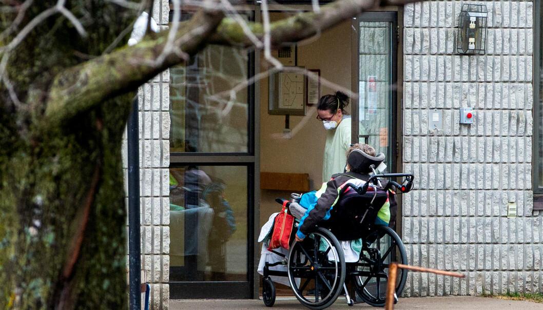 HARDT RAMMET: En ansatt ved Pinecrest-sykehjemmet har vært ute en tur med en av beboerne. Foto: NTB Scanpix