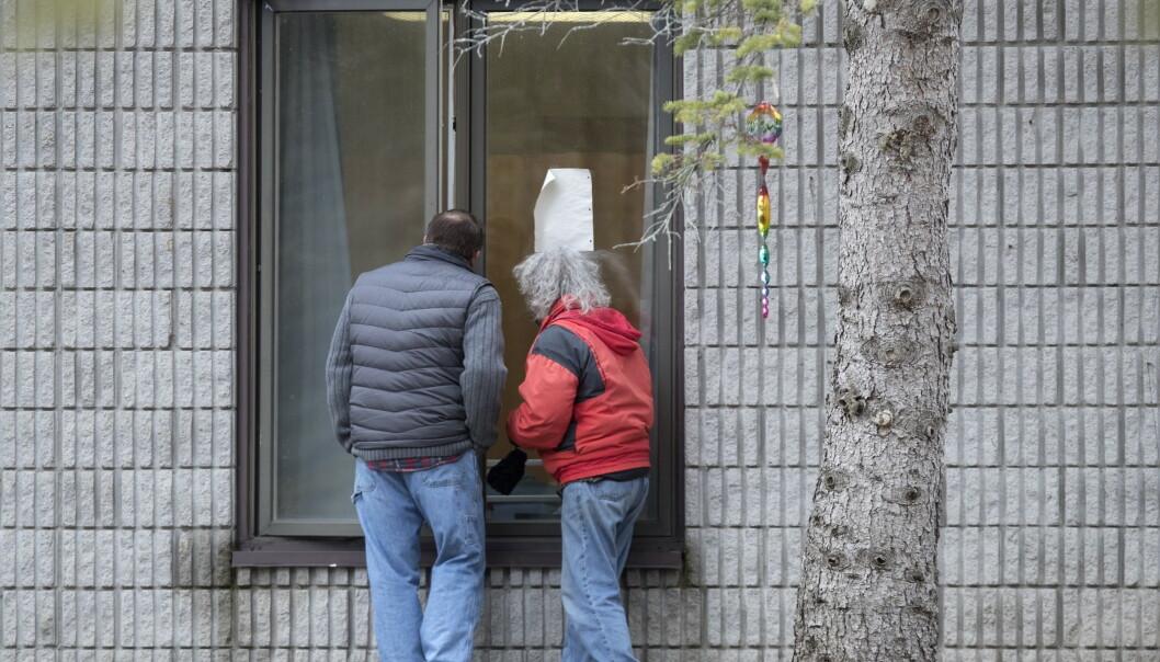BESØK: Pårørende har måttet besøke beboerne på sykehjemmet ved å se dem gjennom vinduet. Foto: Fred Thornhill / The Canadian Press via AP / NTB scanpix