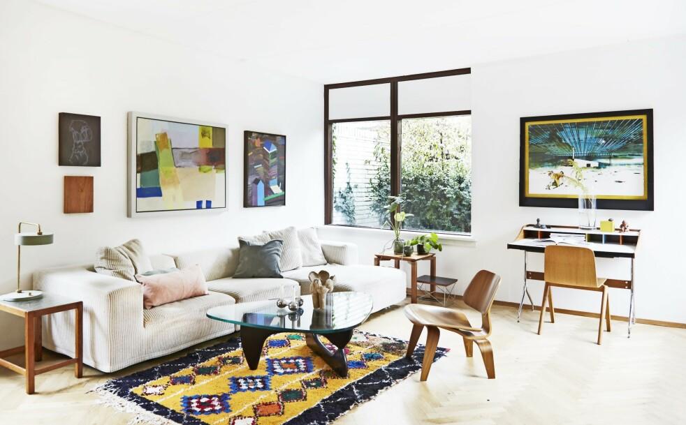 Det er utsyn til hagen gjennom de store vinduene. De to sidebordene kan lett trekkes inntil sofaen når det er behov for dem. Tips! Hvite vegger og en nøytral sofa lar fargerike bilder og et fargerikt teppe få dominere. Det gir en varm og avslappet stemning. FOTO: Nicoline Olsen